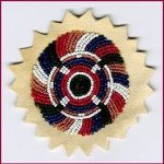 Seed beads in circular pattern on leather patch.