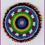 Seed beads in circular pattern on wool and cotton with paper backing for support