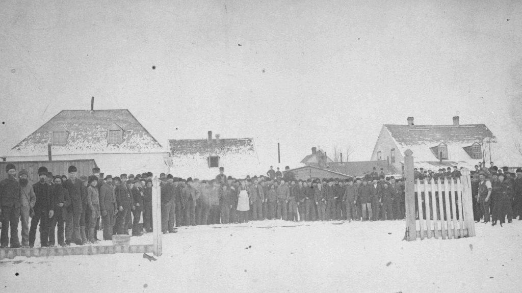 Grain elevator employees standing in front of Hudson's Bay Company buildings circa 1900.