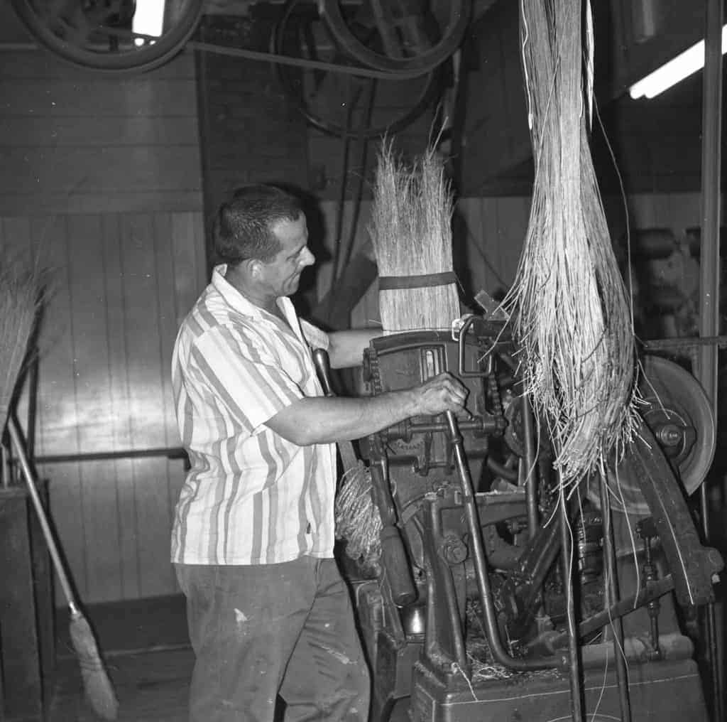 An employee of Lakehead Broom Manufacturing demonstrating the broom-making process in 1969.